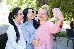 Trois amies merveilleuses de jeune fille font le selfie, photo sur le pho Image libre de droits