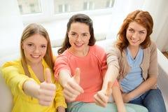 Trois amies montrant des pouces à la maison Images stock