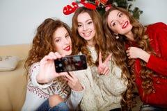 Trois amies prenant un selfie avec le téléphone intelligent Photographie stock libre de droits