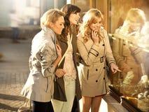 Trois amies regardant la fenêtre de boutique Images stock