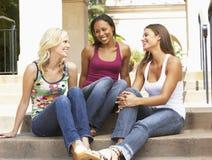 Trois amies s'asseyant sur des opérations de la construction Image stock