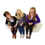 Trois amies s'asseyent sur le divan Image libre de droits