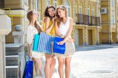 Trois amies sur des achats Trois filles tenant des paniers Photo stock