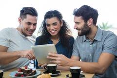 Trois amis à l'aide d'un comprimé numérique Photographie stock libre de droits