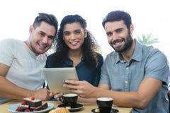 Trois amis à l'aide d'un comprimé numérique Image libre de droits
