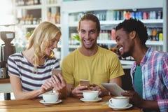 Trois amis à l'aide des téléphones portables tout en ayant la tasse de café Image stock
