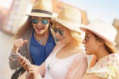 Trois amis à l'aide du smartphone dans la ville Photo libre de droits