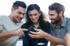 Trois amis à l'aide du téléphone portable dans le café Photo stock