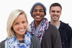 Trois amis à la mode regardant l'appareil-photo et le sourire Images libres de droits