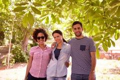 Trois amis à la nuance d'un arbre Images stock
