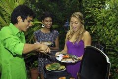 Trois amis à un barbecue Photographie stock libre de droits