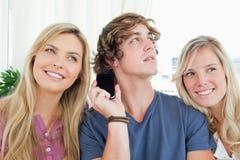 Trois amis écoutant une conversation téléphonique Images stock