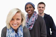 Trois amis élégants regardant l'appareil-photo et le sourire Photos stock