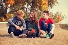 Trois amis adolescents ont un temps d'amusement dans le jour d'or d'automne Images stock