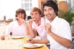 Trois amis appréciant le repas extérieur Images libres de droits