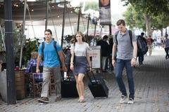 Trois amis avec des valises vont le long de la banque du sud Photos stock
