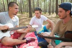 Trois amis avec la guitare se reposant sur la couverture dans la forêt Images stock
