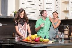 Trois amis ayant l'amusement dans la cuisine Photos libres de droits