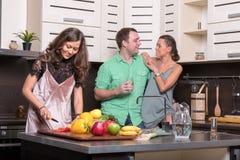 Trois amis ayant l'amusement dans la cuisine Photographie stock libre de droits
