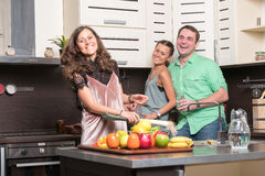 Trois amis ayant l'amusement dans la cuisine Images stock