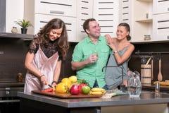 Trois amis ayant l'amusement dans la cuisine Photos stock