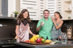 Trois amis ayant l'amusement dans la cuisine Photo libre de droits