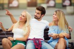 Trois amis ayant l'amusement sur le banc Photo stock