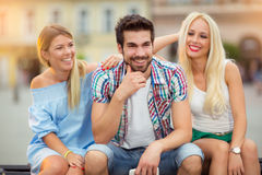 Trois amis ayant l'amusement sur le banc Photos stock