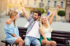Trois amis ayant l'amusement sur le banc Images stock