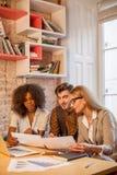Trois amis ayant la conversation d'affaires Les gens tenant des graphiques et des programmes dans leurs mains Image libre de droits