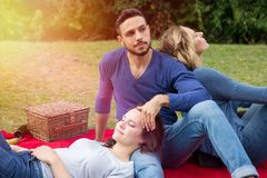 Trois amis ayant un pique-nique et appréciant le soleil Photos stock
