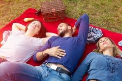 Trois amis ayant un pique-nique et appréciant le soleil Photos libres de droits