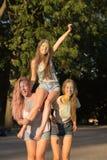 Trois amis blonds adorables de femmes ayant l'amusement au festival de Holi Photographie stock