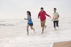 Trois amis courant sur la plage par les eaux affilent, la Chine Photo stock
