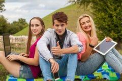 Trois amis détendant et ayant l'amusement en parc Photos stock