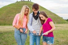 Trois amis détendant et ayant l'amusement en parc Photographie stock libre de droits