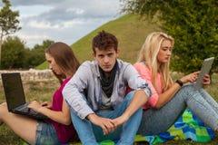Trois amis détendant et ayant l'amusement en parc Images stock
