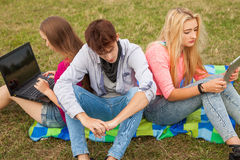Trois amis détendant et ayant l'amusement en parc Photographie stock