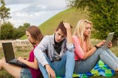 Trois amis détendant et ayant l'amusement en parc Images libres de droits