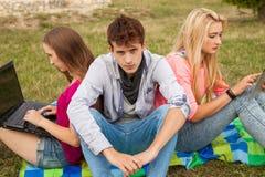 Trois amis détendant et ayant l'amusement en parc Image stock