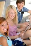 Trois amis d'étudiant avec l'appareil-photo de sourire de comprimé Photo stock