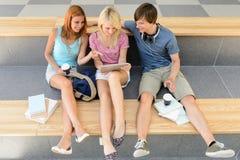 Trois amis d'étudiant universitaire avec le comprimé et le livre Photo libre de droits