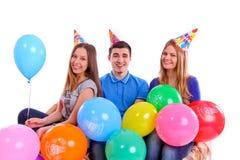 Trois amis dans des chapeaux avec des ballons se reposant sur le divan Image stock