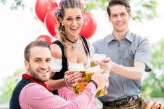 Trois amis dans faire tinter de jardin de bière de Munich Photographie stock