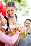 Trois amis dans faire tinter de jardin de bière de Munich Photos stock