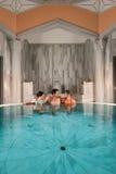 Trois amis dans la piscine ou le bain thermique Photo stock