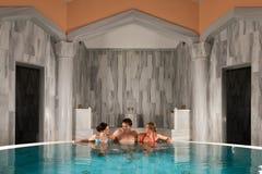 Trois amis dans la piscine ou le bain thermique Photographie stock libre de droits