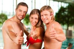 Trois amis dans la piscine publique Image stock