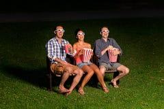 Trois amis dans le cinéma extérieur Image stock