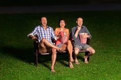 Trois amis dans le cinéma extérieur Photographie stock libre de droits